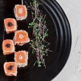 Salmões japoneses Tataki com sésamo e brotos de ervas frescas Em uma placa preta da argila Foto macro, close-up foto de stock