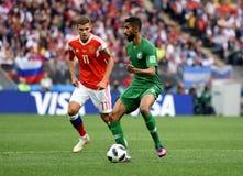 Salman Alfaraj contre le joueur du milieu de terrain russe Roman Zobnin photo stock