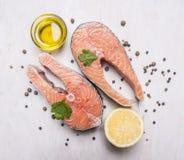 2 salmon стейк, масло, перец и соль, лимон, травы на деревянном деревенском конце взгляд сверху предпосылки вверх Стоковые Фото