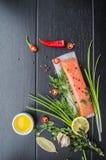 Salmon филе, масло, перец, лимон и зеленые цвета на деревянной черной предпосылке Взгляд сверху Конец-вверх Стоковое Изображение