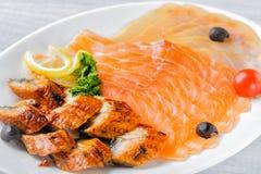 Salmon части филе, угорь conger, части стерляжины служили с лимоном, черными оливками, травами и томатом вишни на белом конце пли Стоковые Фотографии RF