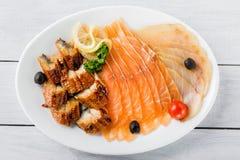 Salmon части филе, угорь conger, части стерляжины служили с лимоном, черными оливками, травами и томатом вишни на белых плите и д Стоковые Изображения