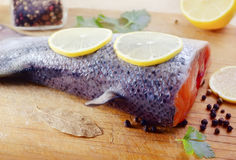 Salmon. Raw salmon with lemon on board Stock Image