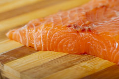 Salmon. A piece of salmon over a wooden chopping board Royalty Free Stock Photography
