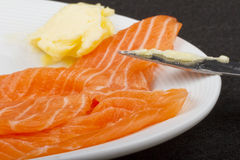 Salmon. A piece of salmon over a white plate, with butter Stock Images