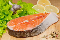 Salmon. Stake of a salmon with seasoning greens and vegetables on a chopping board Stock Image