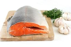 Salmon. Large slab of tail portion of fresh Atlantic salmon on wooden chopping board Stock Photos