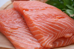 Salmon. Two fresh salmon filets on a wooden cutting board royalty free stock images