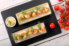 Salmon appetizer with dill dip in puff pastry cake on stone tray Royalty Free Stock Images