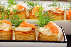 Salmon appetizer with dill dip in puff pastry on stone tray Royalty Free Stock Photo