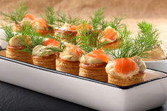 Salmon appetizer with dill dip in puff pastry on stone tray Stock Photography