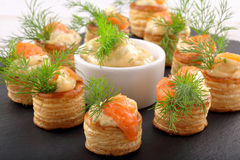 Salmon appetizer with dill dip in puff pastry on stone tray Royalty Free Stock Photos