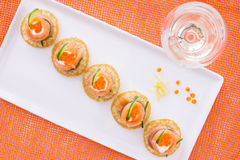 Salmon appetizer and glass of vine, on orange back Stock Image