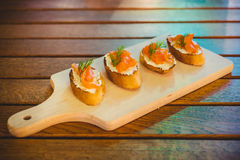 Salmon appetizers. On a wooden plate and table Stock Image