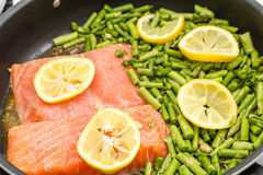 Salmon and Asparagus Cooking in Pan Stock Images