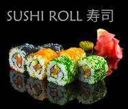 Salmon, avocado and caviar sushi roll on black Royalty Free Stock Images