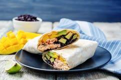 Salmon avocado mango black rice burritos Stock Photo