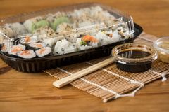 Salmon, avocado and mango inside out California sushi with soy sauce, pickled ginger, soy sauce and wooden chopsticks in plastic royalty free stock images