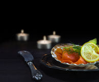 Salmon with avocado in a scallop shell on a silver plate and can Stock Image