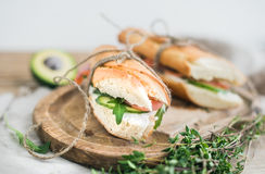 Salmon, avocado and thyme sandwiches in baguette. Salmon and avocado sandwiches with fresh thyme in baguette tied up with a decoration rope on a rustic wooden Royalty Free Stock Images