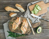 Salmon, avocado and thyme sandwiches in baguette. Salmon and avocado sandwiches with fresh thyme in baguette tied up with a decoration rope on a rustic wooden Stock Images
