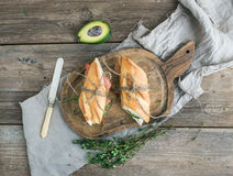 Salmon, avocado and thyme sandwiches in baguette tied up with decoration rope on a rustic wooden board over rough wood background Royalty Free Stock Photos