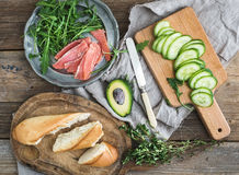 Salmon, avocado and thyme sandwiches in baguette tied up with decoration rope on a rustic wooden board over rough wood background Stock Photo