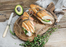 Salmon, avocado and thyme sandwiches in baguette tied up with decoration rope on a rustic wooden board over rough wood background Royalty Free Stock Image