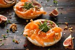 Salmon Bagel Sandwich met fig., tuinkerssalade, okkernoten, roomkaas en korrel op rustieke houten achtergrond Gezond stock fotografie