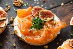 Salmon Bagel Sandwich met fig., tuinkerssalade, okkernoten, roomkaas en korrel op rustieke houten achtergrond Gezond royalty-vrije stock foto's