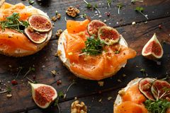 Salmon Bagel Sandwich met fig., tuinkerssalade, okkernoten, roomkaas en korrel op rustieke houten achtergrond Gezond stock foto's