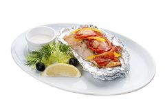 Salmon baked in foil with lemon on a white plate stock photo