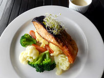 Salmon baked, healthy dish with vegetables. A natural lighting food theme photograph showing a slice of baked salmon to golden brown, served with a variety of Stock Photo