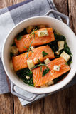 Salmon baked with spinach and roquefort cheese close-up. Vertica Stock Image
