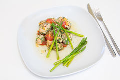 Salmon baked with tomato, capers and asparagus Stock Photos
