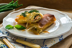 Salmon and basil butter filo parcels. With green beans Stock Photo