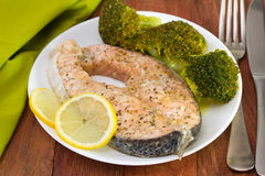 Salmon with broccoli. And lemon on the white plate stock images
