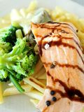 Salmon with broccoli, noodle and bechamel sauce Stock Photos