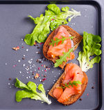 Salmon with brown bread over black background Stock Photo