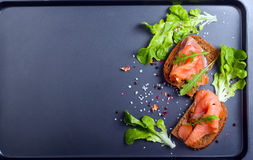 Salmon with brown bread over black background Stock Images