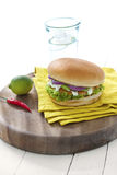 Salmon burger. Salmon or chicken burger with green salad and red onions dressed with tartar sauce stock photo