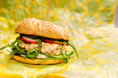 Salmon burger. Salmon and fresh vegetables burger Royalty Free Stock Images