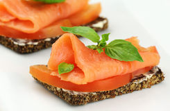 Salmon canape. Delicious canape with smoked salmon, tomatoes and fresh basil stock images