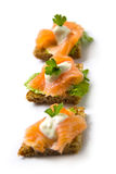 Salmon canape. Three small salmon canapé with smoked salmon, parsley, white sauce and lettuce leaves on rye bread stock photography