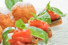 Salmon canape with basil. Three salmon canape with basil on glass plate stock images