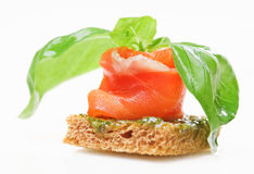 Salmon canape with basil. Isolated on white royalty free stock photography