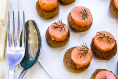Salmon appetizers. Salmon canape with herbs on a buffet table Stock Photography