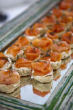 Salmon canapes. On a mirror platter tray Royalty Free Stock Photo