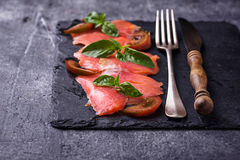 Salmon carpaccio with basil and tomato Stock Photos