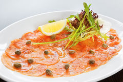 Salmon carpaccio. With rucola, lemon and lettuce royalty free stock image